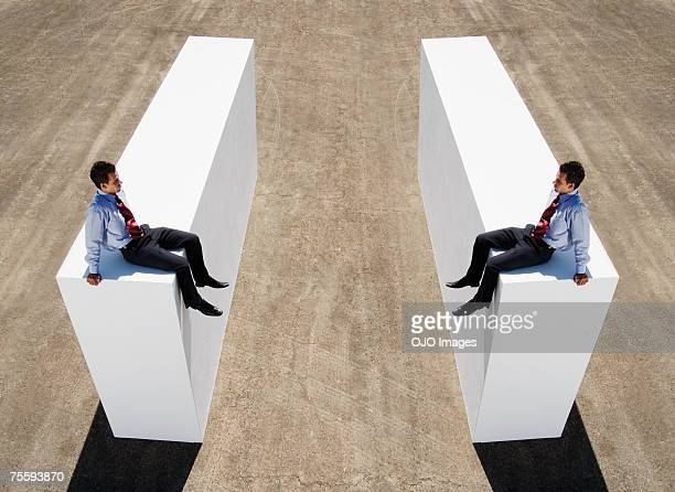 An identical split image of a businessman on a wall