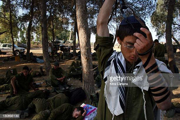 An IDF soldier takes part in early morning prayers at a base just outside of the Gush Katif settlement bloc on July 17 2005 Thousands of Israeli...
