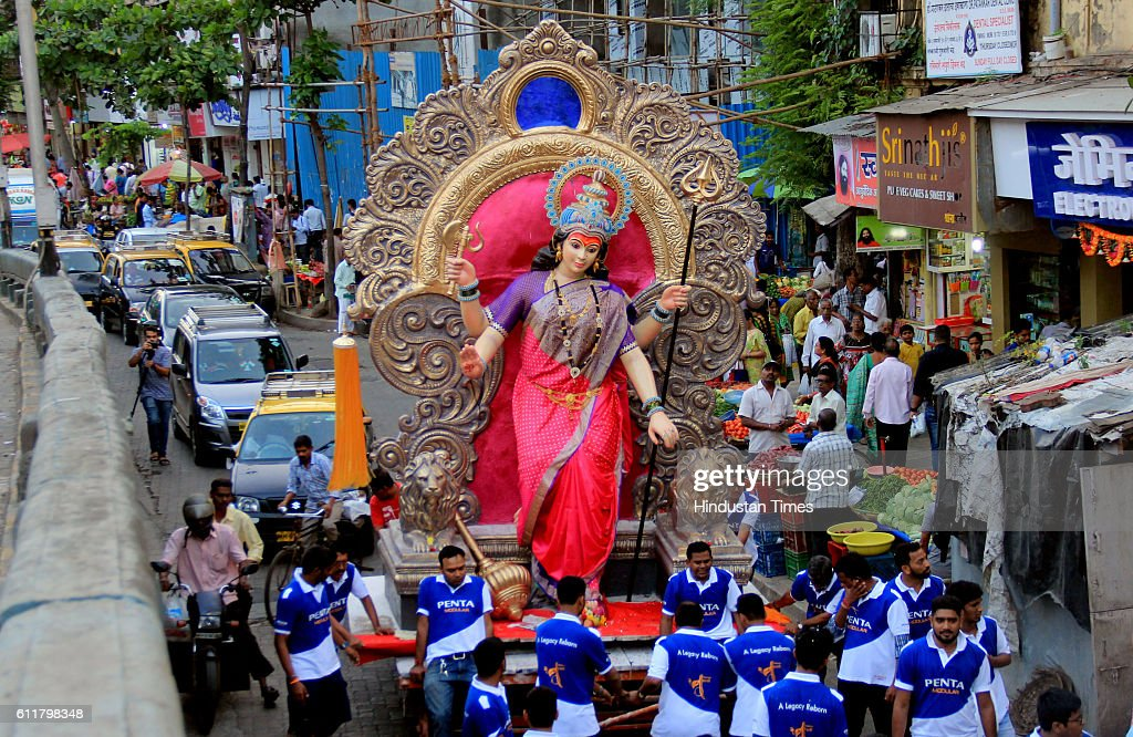 An idol of a Goddess Durga being carried by the devotees from a Parel Workshop to the pandal at Chira Bazar before the Navratri Festival, on September 30, 2016 in Mumbai, India. The first day of the Navratra started with the worship of Shailputri Swaroop of Goddess Durga with full religious rites amidst chanting of Jaikaras by the large number of devotees who had lined up for the first darshan since previous night. Navaratri is a festival dedicated to the worship of the Hindu deity Durga. The word Navaratri means 'nine nights' in Sanskrit, nava meaning nine and ratri meaning nights.