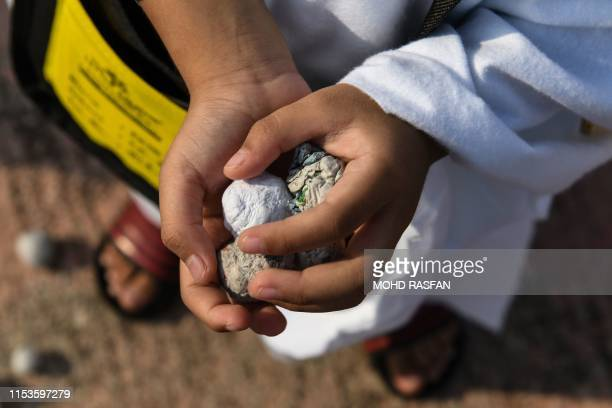 An Ihramclad Muslim boy carries mock stones made from papier mache before performing the ritual of stoning the devil during an educational simulation...