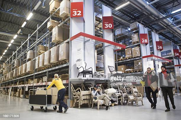 An IKEA employee and customers roam the warehouse at the IKEA store in Malmo Sweden on Monday January 21 2013 The privately held Swedish company is...