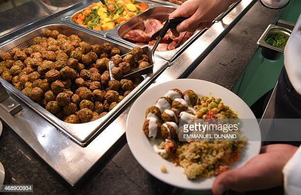 An IKEA employee serves the new IKEA vegetarian meatballs during a worldwide launch at IKEA Anderlecht on April 8 2015 IKEA who withdrew its...