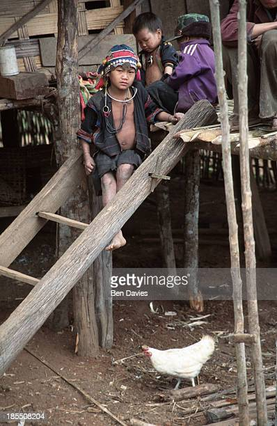 An Iko girl sits on a wooden ladder outside her thatched home in the village of Phouyair a three day walk from Muang Sing in Northern Laos