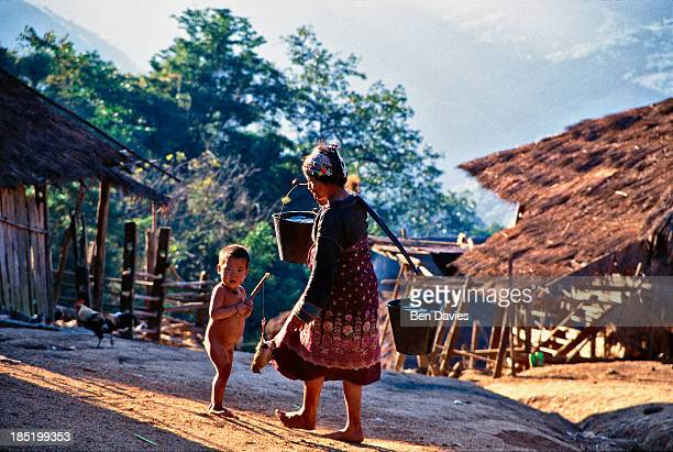 An Iko woman carries water from the river to her thatched home in the village of Phouyair a three day walk from Muang Sing in the North of Laos The...