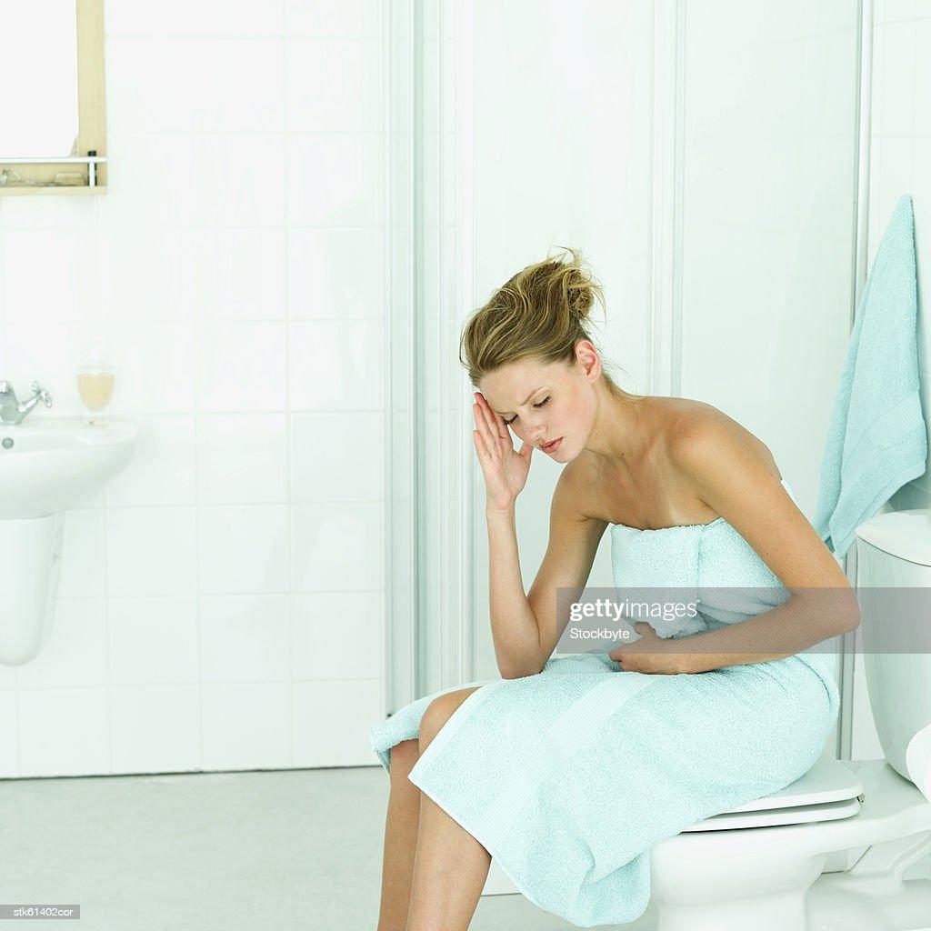 an ill woman in the bathroom : Stock Photo