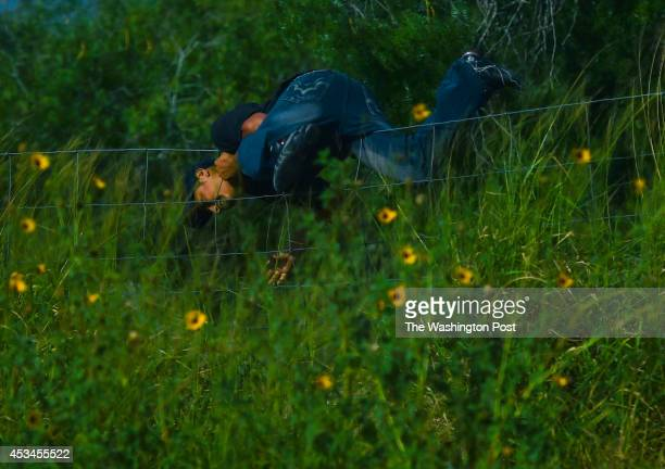 An illegal immigrant jumps a fence while fleeing from Deputy Elias Pompa on July 22 2014 in Falfurrias TX The Brooks County Sheriff's Office with its...