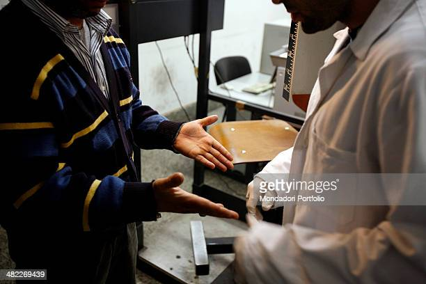 An illegal immigrant stopped by the police without the papers in order and brought at the police station shows his hands to a man in scrubs the...