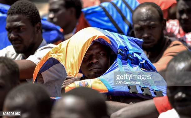 TOPSHOT An illegal migrant who was rescued by Libyan coast guards at covers his head from the sun upon arrival at a migration detention and shelter...