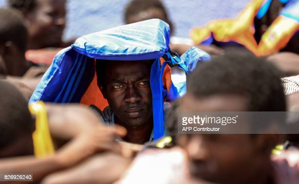 An illegal migrant who was rescued by Libyan coast guards at covers his head from the sun upon arrival at a migration detention and shelter facility...