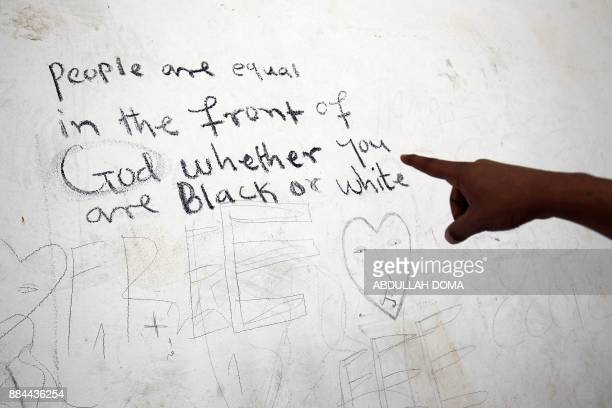 An illegal subSaharan migrant shows writings on a wall as he waits at the Qanfouda detention centre in the southern outskitrs of Benghazi before...