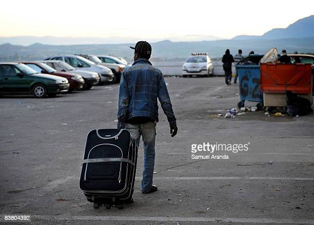 An illigal immigrant rolls his belongings behind him as he arrives at an aid center November 20 2008 in Jaen Spain Jobs such as the yearly olive...
