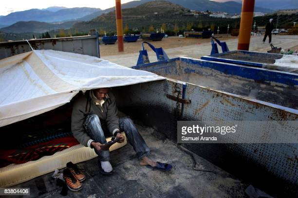 An illigal immigrant sits in his shelter November 20 2008 in Jaen Spain Jobs such as the yearly olive harvest traditionally undertaken by immigrant...