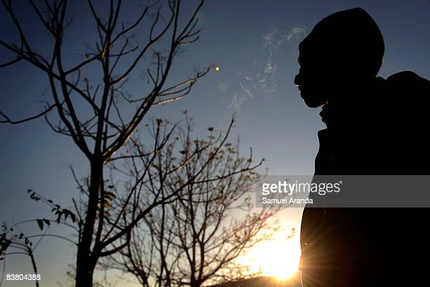 An illigal immigrant smokes a cigarette as the sun rises November 20 2008 in Jaen Spain Jobs such as the yearly olive harvest traditionally...