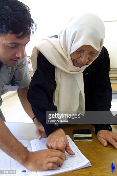 An illiterate Jordanian woman registers to vote with the imprint of her thumb at a polling station June 17 2003 in Irbid Jordan Jordanians are...
