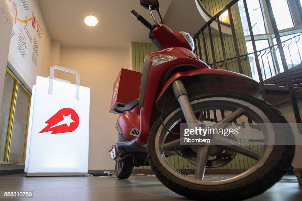 An illuminated bagshaped logo and a delivery moped motorcycle stand in the reception area of the Delivery Hero AG headquarter offices in Berlin...