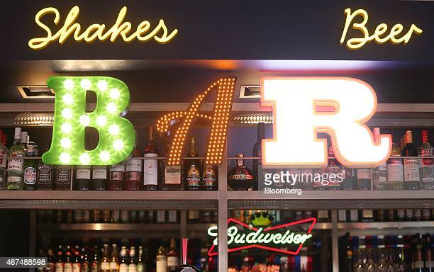 An illuminated 'Bar' sign sits above bottles of spirits at the cocktail bar inside a Pizza Hut restaurant owned by Yum Brands Inc at the company's...