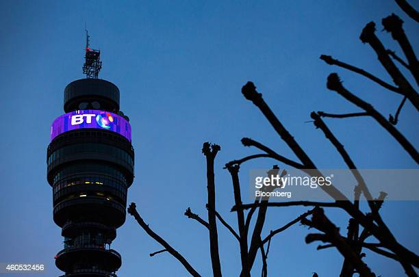 An illuminated BT logo sits above communications equipment on the BT Tower operated by BT Group Plc at dusk in London UK on Monday Dec 15 2014 BT...
