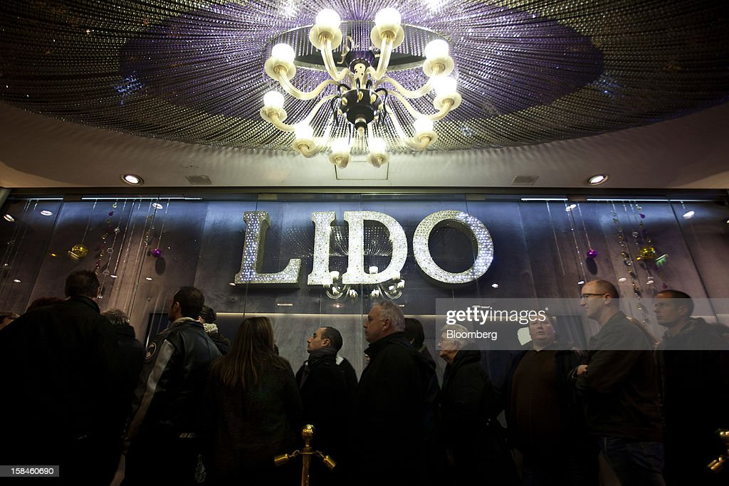 An illuminated chandelier hangs above visitors as they queue to enter the Lido cabaret house on the Champs-Elysees in Paris, France, on Saturday, Dec. 15, 2012. The French minister for energy and environment unveiled a proposal for lights in and outside shops, offices, and public buildings -- including the flagship Louis Vuitton store and the Lido cabaret house on Paris's Avenue des Champs Elysees -- to be turned off between 1 a.m. and 7 a.m. starting in July. Photographer: Balint Porneczi/Bloomberg via Getty Images