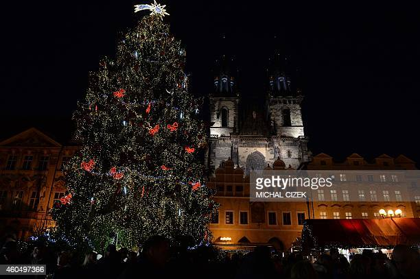 An illuminated Christmas tree is seen at the market at the Old Town Square in Prague on December 15 2014 In the background the Church of Mother of...