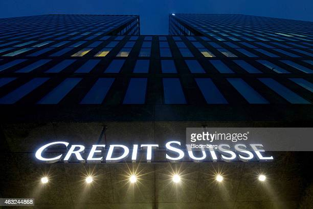 An illuminated Credit Suisse logo sits above the entrance to a Credit Suisse Group AG office building in Zurich Switzerland on Thursday Feb 12 2015...