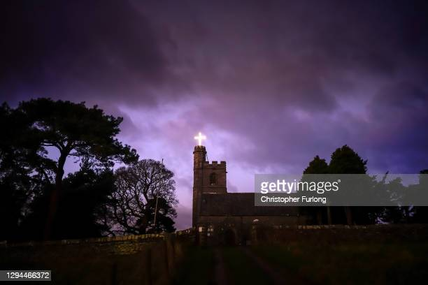 An illuminated cross adorns the top of the tower at St Patrick's Church in the village of Preston Patrick, Cumbria, on January 04, 2021 in...