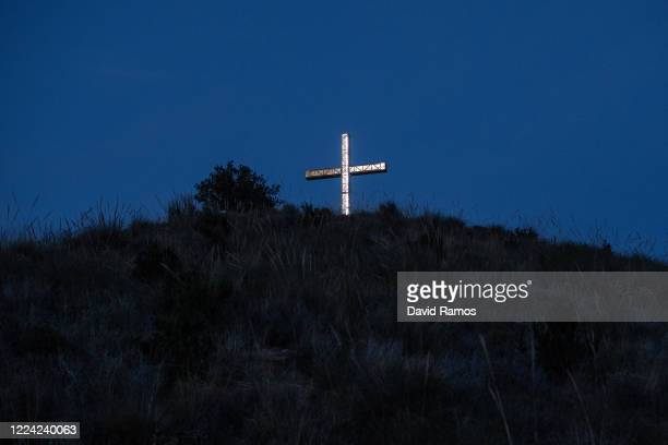 An Illuminated cross sits on the summit of Sierra Gelada hill on May 11 2020 in Benidorm Spain Some parts of Spain have entered the socalled Phase...