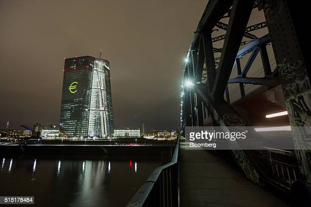 An illuminated euro currency symbol is projected on to the European Central Bank headquarters during a rehearsal for the Luminale light festival in...