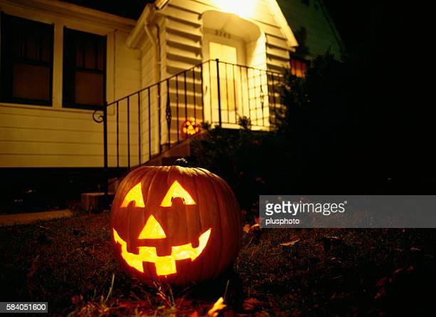 an illuminated jack o'lantern sitting on a front lawn at night. iowa, usa - plusphoto stock pictures, royalty-free photos & images