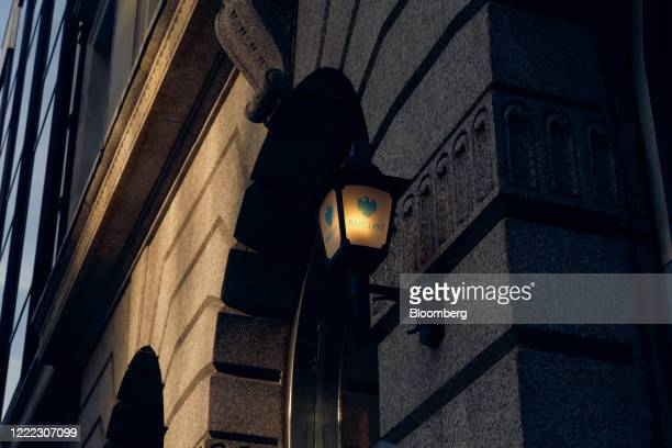 An illuminated lamp hangs outside a branch of Barclays Plc bank in the City of London UK on Tuesday June 23 2020 Many of the financial districts most...