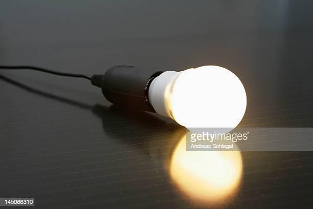 an illuminated light bulb on a solar panel - bombilla de bajo consumo fotografías e imágenes de stock