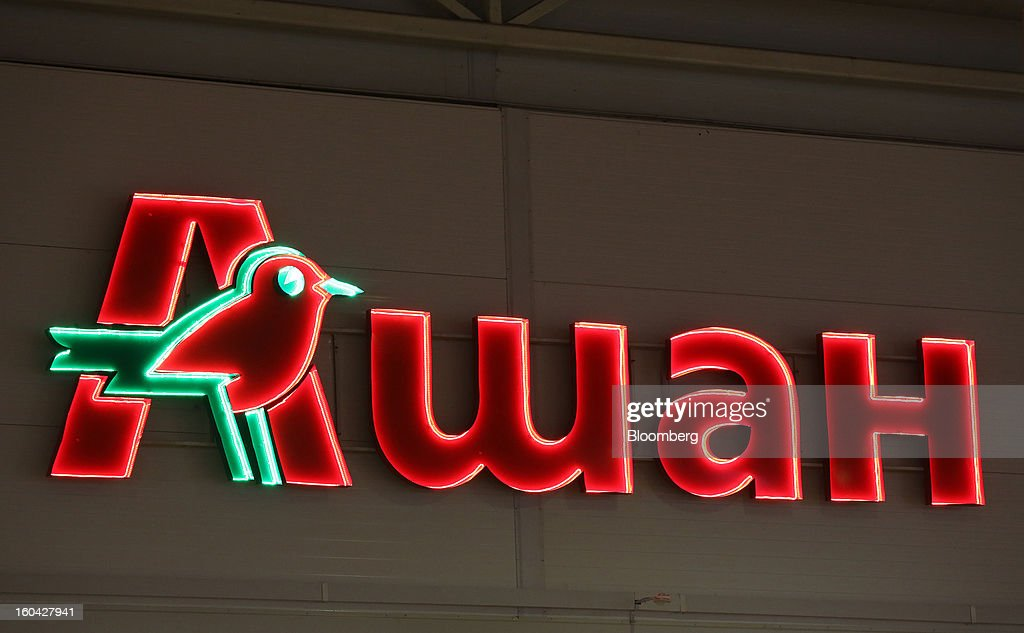 An illuminated logo hangs above the entrance to an Auchan Groupe SA store at the MEGA Belaya Dacha shopping complex, constructed by the real estate development arm of Inter Ikea Systems BV and one of Europe's largest malls, in Moscow, Russia, on Thursday, Jan. 31, 2013. Russian shopping-mall construction may climb to a record this year as retailers take advantage of rising sales by moving into bigger, more modern buildings, Cushman & Wakefield Inc. said. Photographer: Andrey Rudakov/Bloomberg via Getty Images
