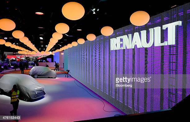 An illuminated logo hangs near covered automobiles at the Renault SA display stand during preparations ahead of the 84th Geneva International Motor...