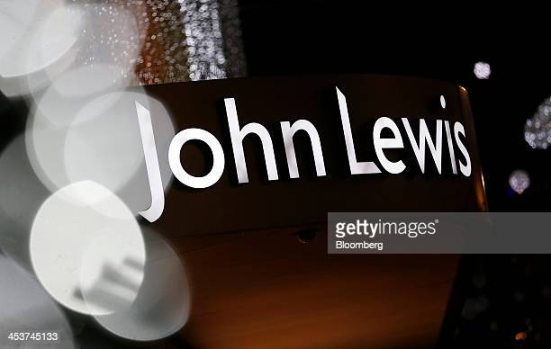 An illuminated logo sits above the entrance to a John Lewis Plc department store on Oxford Street in London UK on Wednesday Dec 4 2013 The UK economy...