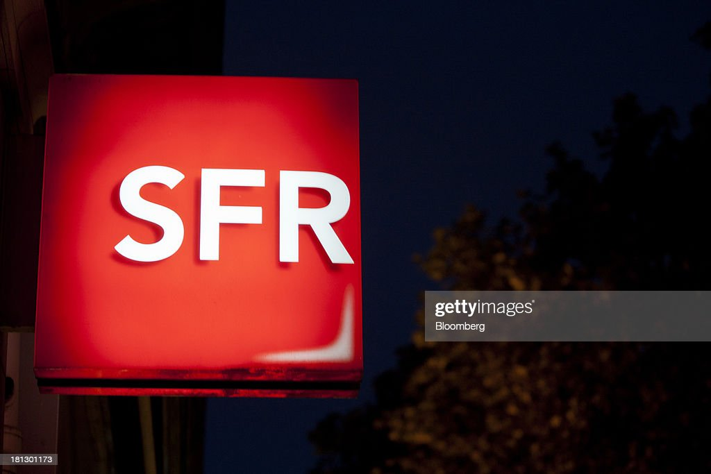 An illuminated logo sits on display outside an SFR store, a mobile-phone unit of Vivendi SA, in Paris, France, on Thursday, Sept. 19, 2013. Bank of France General Council member Bernard Maris said France will end up restructuring its debt as tax 'optimization' by large companies including Google Inc. will leave too big a burden on the middle class. Photographer: Balint Porneczi/Bloomberg via Getty Images