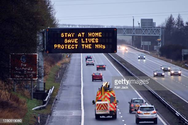 """An illuminated motorway sign carries the coronavirus lockdown """"Stay At Home"""" message, on January 10, 2021 in Dunfermline, Scotland. Scottish First..."""