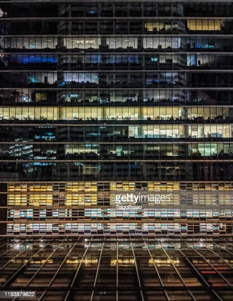 シンガポールの夜に照らされたオフィスビルで、空の机で青と黄色のコントラストを見せる - カーキグリーン ストックフォトと画像