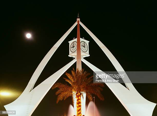 an illuminated palm tree is seen at the center of a tapering structure with clocks at the top. - clock tower stock pictures, royalty-free photos & images