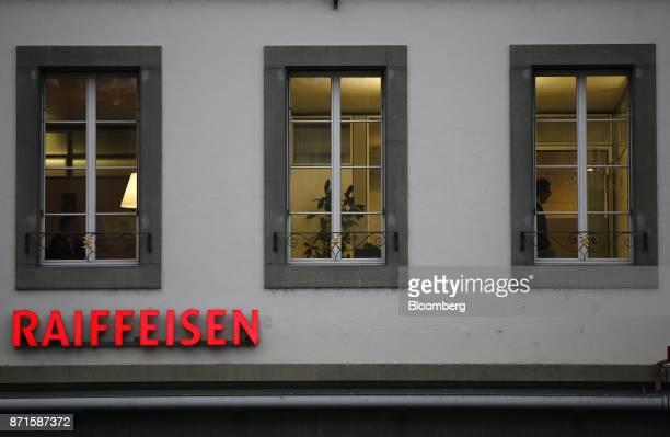 An illuminated Raiffeisen logo hangs above the entrance to a Raiffeisen Schweiz Genossenschaft bank branch in Bern Switzerland on Tuesday Nov 7 2017...