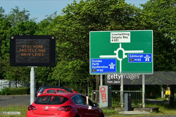 """An illuminated road sign emphasises the underlying message in Scotland remains """"Stay At Home"""", as the Scottish Government eases some Covid-19..."""