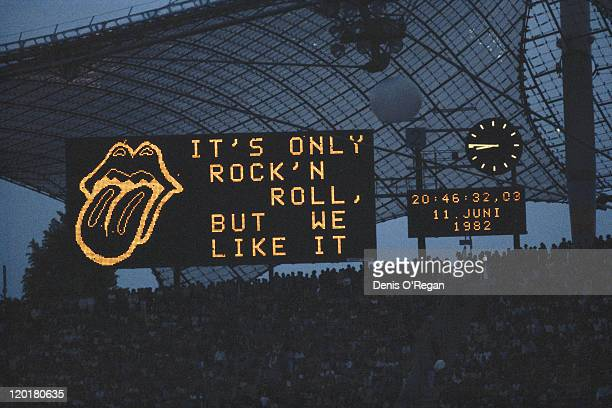 An illuminated sign reading 'It's only rock 'n' roll but we like it' with a Rolling Stones tongue and lips logo at the Olympiastadion Munich during a...
