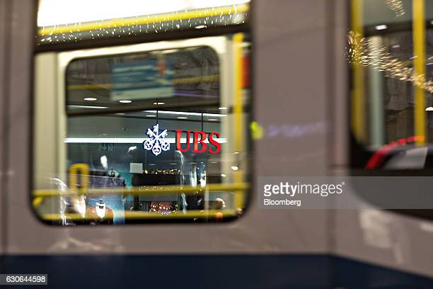 An illuminated sign sits beyond the window of a passing tram as it hangs in front of an entrance to the UBS Group AG headquarters in Zurich...