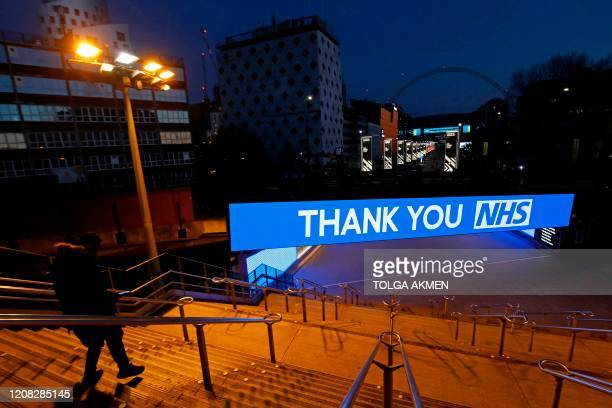 An illuminated sign thanking the NHS is pictured across Olympic Way the road to Wembley Stadium in London on March 26 as a sign of public admiration...
