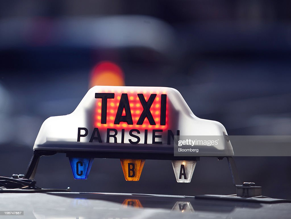 An illuminated taxi sign is seen on top of an automobile outside the Paris Nord train station in Paris, France, on Tuesday, Nov. 20, 2012. France's government bonds fell, with 10-year yields rising the most in a month, after Moody's Investors Service lowered the nation's top credit rating, citing a worsening economic growth outlook. Photographer: Balint Porneczi/Bloomberg via Getty Images
