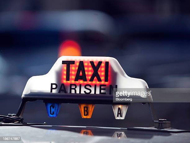 An illuminated taxi sign is seen on top of an automobile outside the Paris Nord train station in Paris, France, on Tuesday, Nov. 20, 2012. France's...
