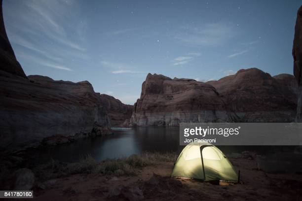 An illuminated tent in the foreground of dusk setting over Escalante Canyon Lake Powell