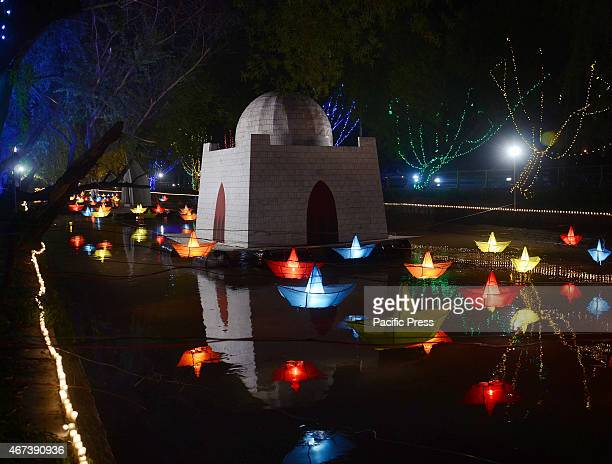 An illuminated view of the floats and lining trees decorated with festive lights in the canal in connection to the spring festival Lahore is the...