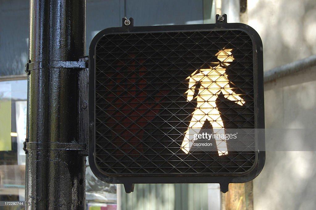 An illuminated walk street sign : Stock Photo