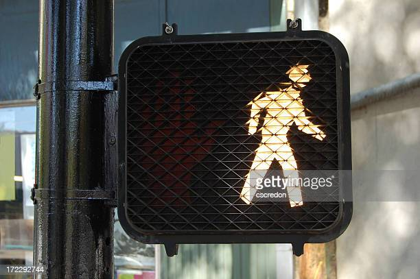 an illuminated walk street sign - pedestrian crossing stock photos and pictures