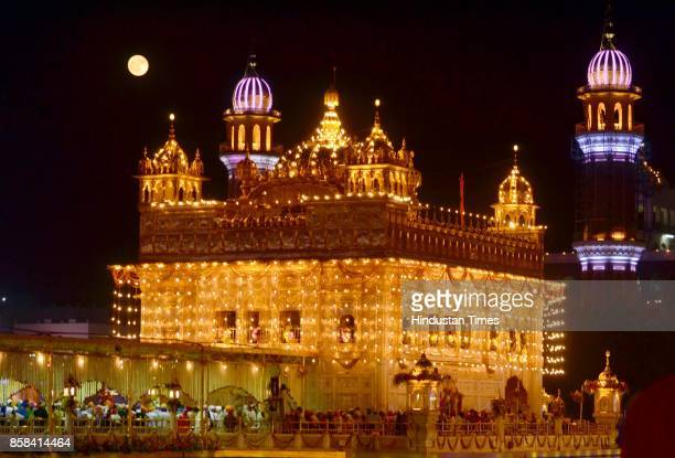 An illuminated with new LED lights Golden Temple reflecting divine view in combination with moon on the eve of birth anniversary of Guru Ram Das...