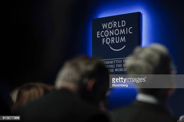 An illuminated World Economic Forum sign hangs on the wall during a panel session on day three of the World Economic Forum in Davos Switzerland on...